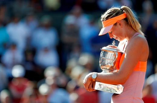 Maria Sharapova of Russia holds the trophy after winning the French Open tennis tournament in Paris in this June 7, 2014 photo