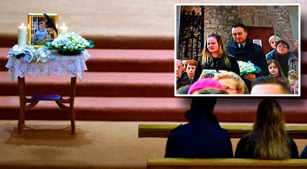 A photo of smiling Baby Karol on the altar at St Mary's Cathedral. (Inset) Mother Anna Rozycka carries a photograph of her 11-month-old son to the altar