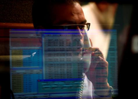 A Pakistani stockbroker talks on his phone during a trading session at the Pakistan Stock Exchange (PSE) in Karachi. Photo: AFP/Getty Images