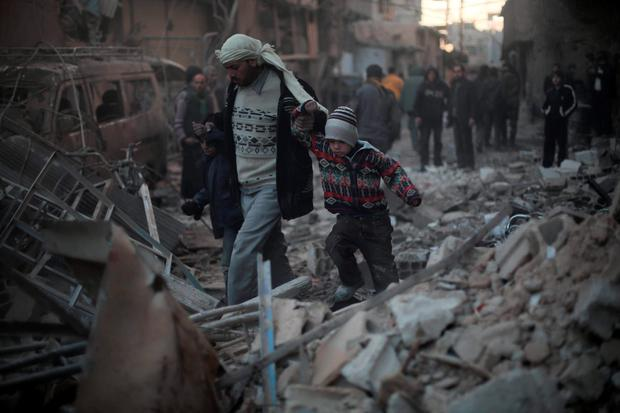 Man holding his child's hand as they walk through rubble after surviving an airstrike in Eastern Ghouta, Syria, as the charity launches a new report into life in besieged areas in Syria, where more than 250,000 children remain trapped without food, medicine or electricity