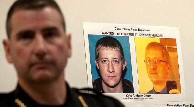 Coeur d'Alene Police Chief Lee White addresses the media, with a photo of Kyle Odom in the background.