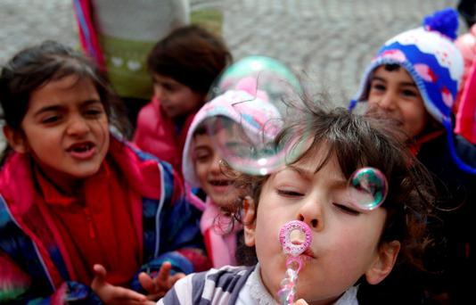 A migrant girl blows soap bubbles by the highway waiting to leave toward Croatia from the Adasevci, about 100 kms west from Belgrade, Serbia (AP Photo/Darko Vojinovic)