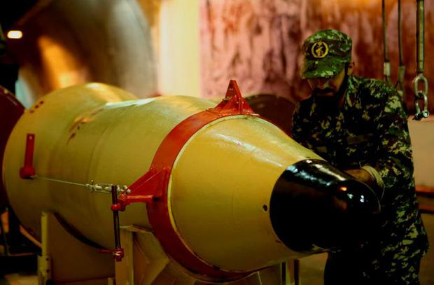 A member of the Iranian Revolutionary Guards checks a missile inside an underground depot in Iran Credit: Sepahnews.com (REUTERS)