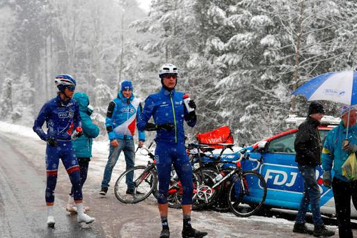 Cyclists of FDJ team have a break under the snow during the third stage of the 74th edition of the Paris-Nice cycling race between Cusset and Mont Brouilly