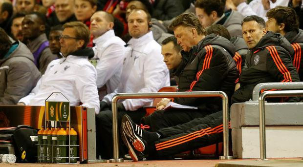 Manchester United manager Louis van Gaal and assistant manager Ryan Giggs look dejected as Liverpool manager Juergen Klopp looks on