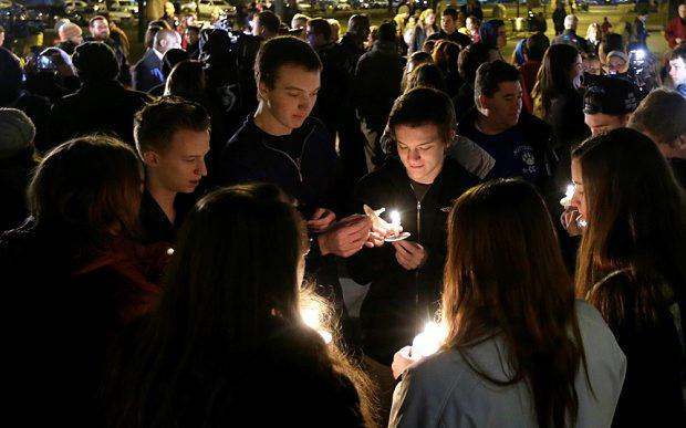 People gather in Bronson Park in Kalamazoo, Mich., Monday, Feb. 22, 2016, for a candlelight vigil for the victims of a series of random shootings in the Kalamazoo area