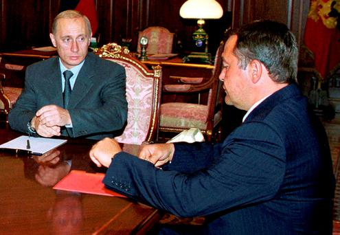 Russian President Vladimir Putin (L) listens during his meeting with Minister for Mass Media Mikhail Lesin (R) in the Kremlin in this August 28, 2000 file photo