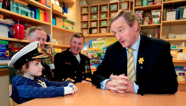Taoiseach Enda Kenny with Izzie Swail (5) from Wicklow, Brigadier General Nick Berry and Vice-Admiral Mark Mellett at Tallaght Hospital School for the delivery of the last flag in the Flags for Schools Initiative as part of the 1916 commemorations. Photo: Maxwells