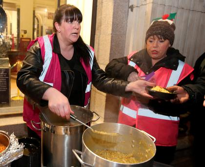 Volunteers Sinead Kane and Tracey Byrne hand out hot meals to the homeless outside the GPO in Dublin. Photo: Damien Eagers