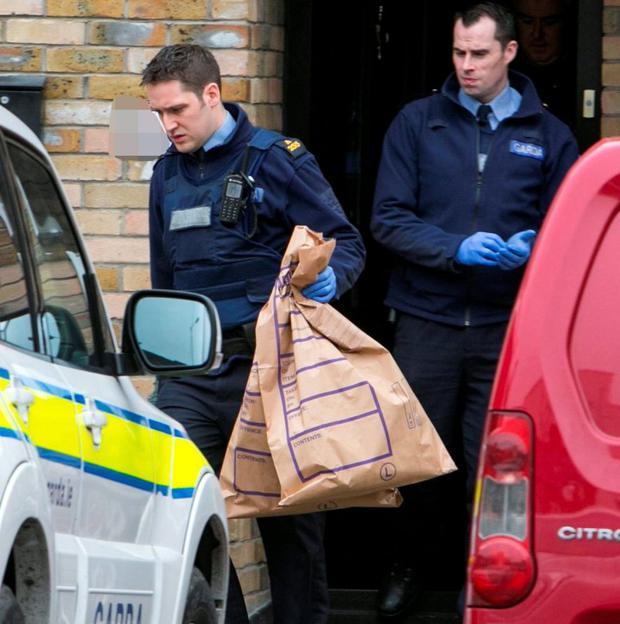 Gardai remove evidence after inspecting a premises during raids in which sniffer dogs were utilised