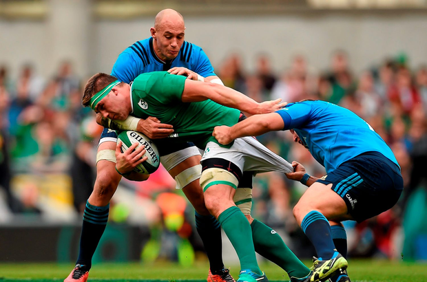CJ Stander, Ireland, is tackled by Sergio Parisse, left, and Davide Giazzon, Italy