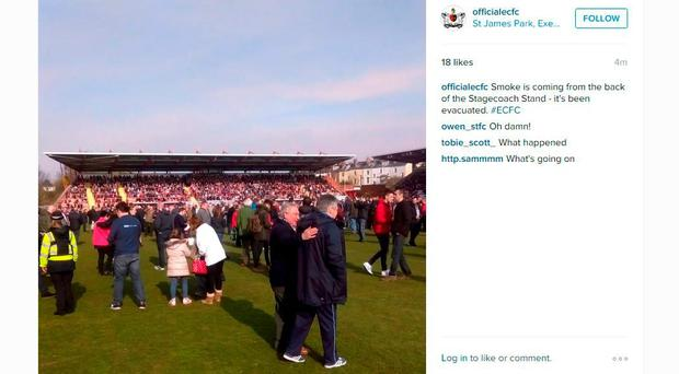 Screen grab taken from the Instagram page of Exeter City FC (officialecfc) of fans on the pitch after smoke was seen coming from the back of the Stagecoach Stand