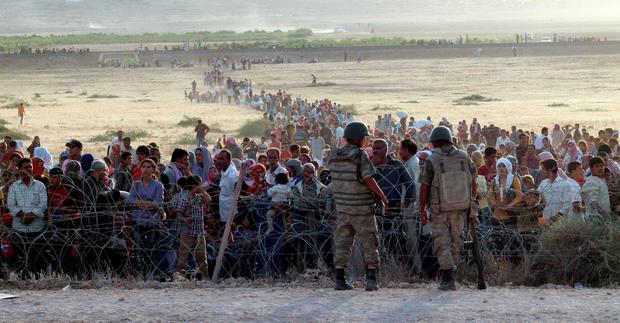 Behind the wire: Turkish soldiers stand guard as Syrians wait behind the border fences near the southeastern town of Suruc in Sanliurfa province, Turkey. Photo: Kadir Celikcan/Reuters