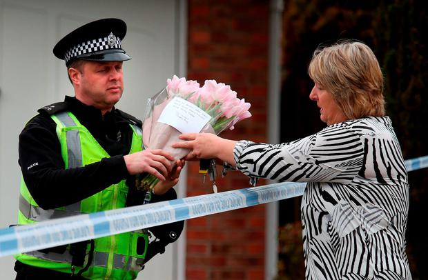 A woman leaves some flowers with police Credit: Andrew Milligan/PA Wire