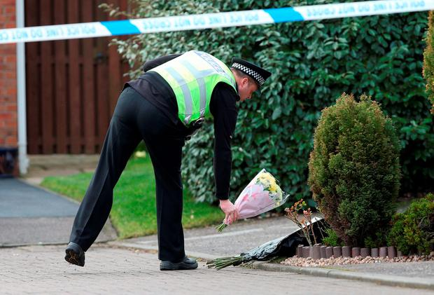 A police officer moves flowers Credit: Andrew Milligan/PA Wire
