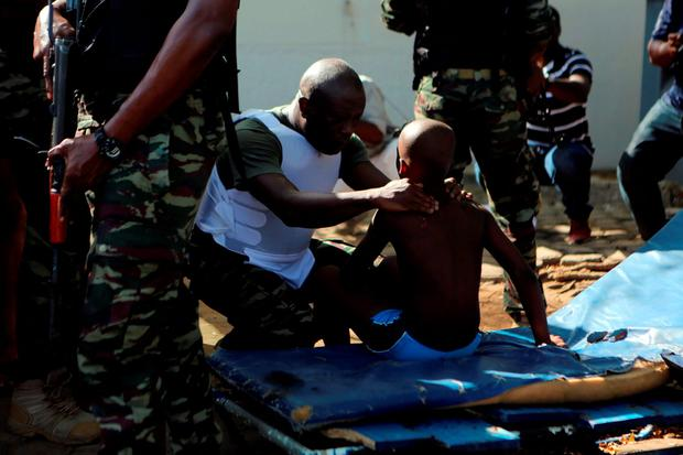 A soldier comforts an injured boy in Bassam, Ivory Coast, March 13, 2016. REUTERS/Joe Penney