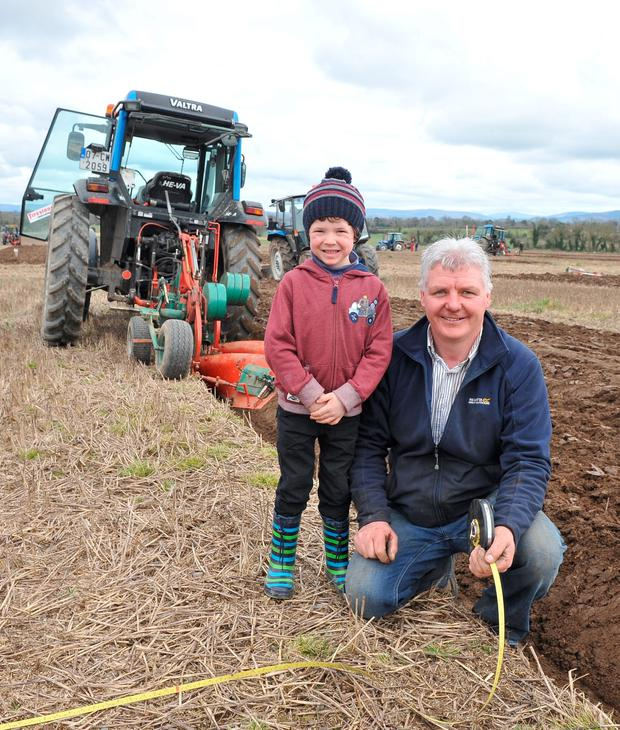 World champion Eamonn Tracey measures up as he finishes his plot at the Co Carlow ploughing championship with a little help from his no 1 fan Saran Buttle from Ballylynan. Eamon went on to win in Carlow and also won in Wexford on Saturday. Photo Roger Jones.