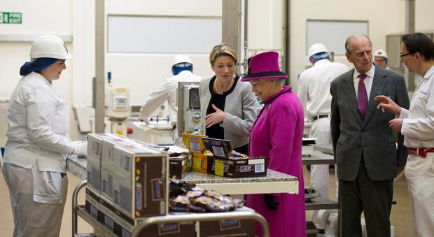 Britain's Queen Elizabeth II (CR) accompanied by Prince Philip, Duke of Edinburgh (2R), are shown chocolate products by Fiona Dawson (C) President of Mars Chocolate UK in the pilot plant, part of the research and development, during a visit to Mars Chocolate UK in Slough, southern England on April 5, 2013. The Queen and the Duke of Edinburgh visited the Mars factory in Slough that has been producing chocolate for over 80 years. A plaque was unveiled to commemorate the visit in which the Queen toured the facility and spoke with members of staff. Cook has worked for Mars for 69 years. (PHOTO: ADRIAN DENNIS/AFP/Getty Images)
