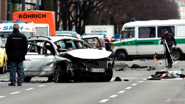 Rescuers and police officers work around a damaged car after a blast caused by an explosive device killed its driver travelling down a street in central Berlin on March 15, 2016