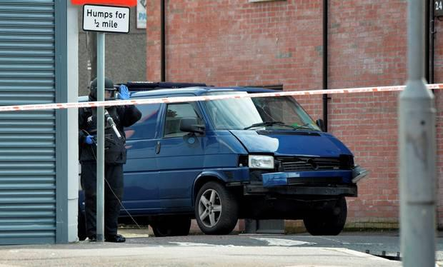 A bomb disposal unit officer inspects the damaged van following a suspected car bomb attack on a prison officer at Hillsborough Drive on March 4, 2016 in Belfast, Northern Ireland. (Photo by Charles McQuillan/Getty Images)