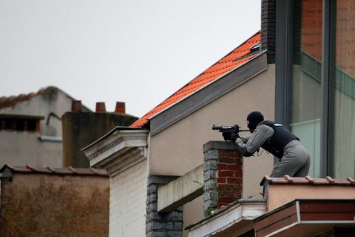 A Belgium police officer secures the area from a rooftop near the scene where shots were fired during a police search of a house in the suburb of Forest near Brussels, Belgium