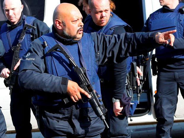 Police at the scene where shots were fired during a police search of a house in the suburb of Forest near Brussels