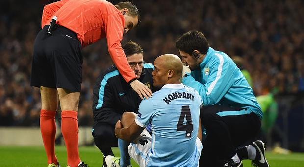 MANCHESTER, ENGLAND - MARCH 15: An injured Vincent Kompany of Manchester City (4) is given treatment during the UEFA Champions League round of 16 second leg match between Manchester City FC and FC Dynamo Kyiv at the Etihad Stadium on March 15, 2016 in Manchester, United Kingdom. (Photo by Laurence Griffiths/Getty Images)
