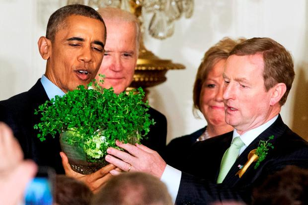 President Barack Obama with Vice President Joe Biden, and Enda Kenny with his wife Fionnuala Kenny, hold up a bowl of shamrocks during a reception in honor of St. Patrick's Day in the East Room of the White House in Washington. (AP Photo/Jacquelyn Martin)