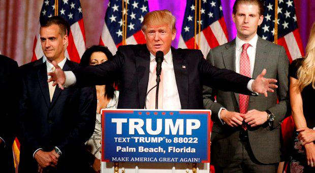 Republican U.S. presidential candidate Donald Trump stands between his campaign manager Corey Lewandowski (L) and his son Eric (R) as he speaks about the results of the Florida, Ohio, North Carolina