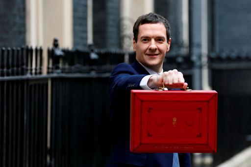 Britain's Chancellor of the Exchequer George Osborne holds up his budget case for the cameras on Downing Street yesterday. Photo: Reuters