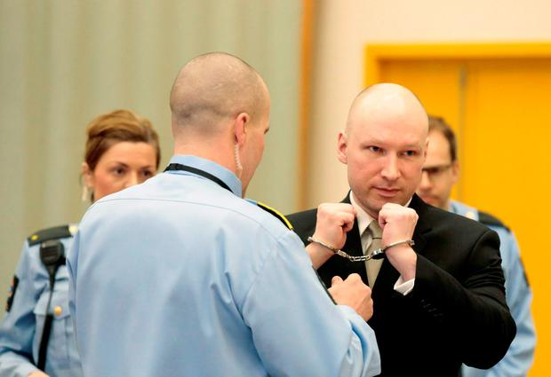 Mass killer Anders Behring Breivik has his handcuffs removed inside the court room in Skien prison, Norway
