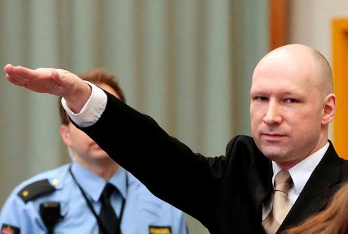Anders Behring Breivik gestures as he enters a courtroom in Skien, Norway