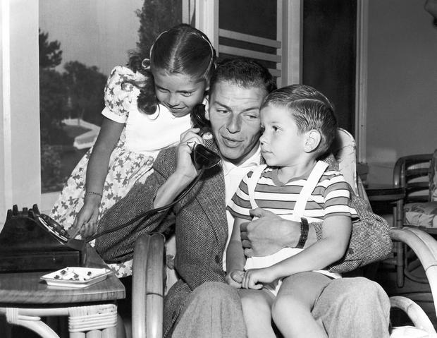 In this 1948 file photo, Frank Sinatra holds a telephone with his children, Nancy and Frank Jr., in the Hollywood area of Los Angeles. Frank Sinatra Jr., who carried on his famous father's legacy with his own music career, died unexpectedly of cardiac arrest while on tour Wednesday, March 16, 2016, his family said. He was 72