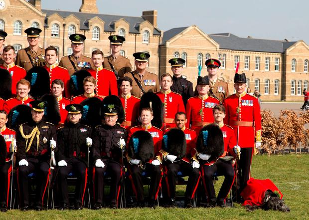 The Duke of Cambridge poses for the Officer's Mess group photo with the Irish Guards during a visit to Cavalry Barracks in Hounslow, west London
