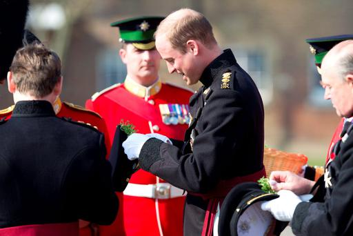 The Duke of Cambridge attaches a sprig of shamrock to his hat as he presents the Irish Guards with shamrocks during a visit to Cavalry Barracks in Hounslow, west London, for the regiment's St Patrick's Day Parade