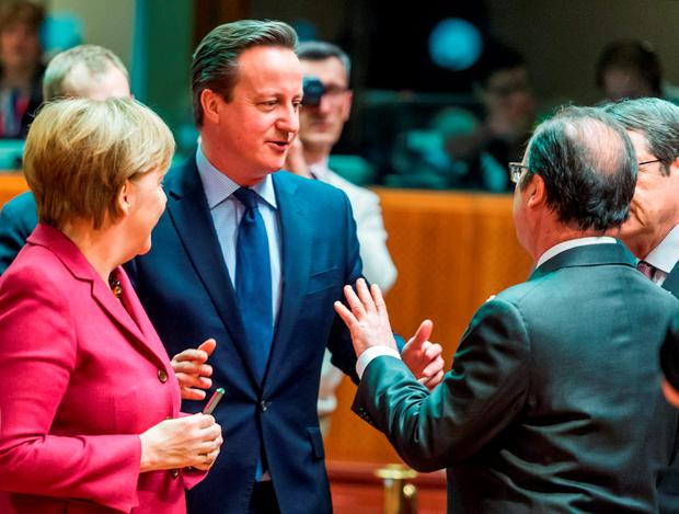 German Chancellor Angela Merkel, left, speaks with French President Francois Hollande, right, and British Prime Minister David Cameron, center, during a round table meeting at an EU summit in Brussels on Thursday (AP Photo/Geert Vanden Wijngaert)
