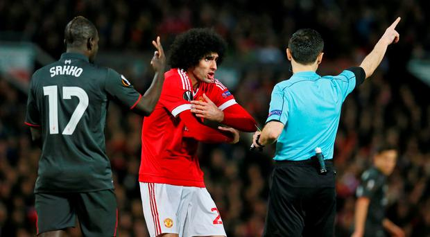 Manchester United's Marouane Fellaini gestures to referee Referee Milorad Mazic