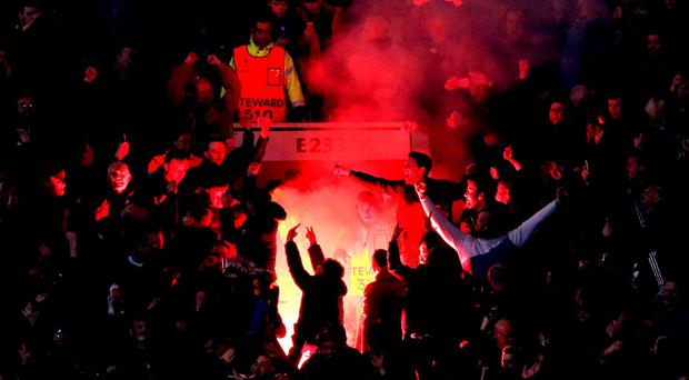 Liverpool fans let off a red flare in the stands at Old Trafford