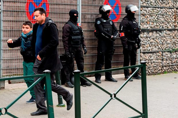 Police officers guard an entrance of a school during a raid in the Molenbeek neighborhood of Brussels, Belgium