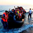Migrants arrive in Kos, Greece, in a rubber dinghy. Photo: PA