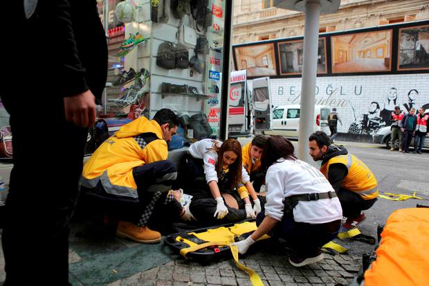 A man is helped by emergency services members following a suicide bombing in a major shopping and tourist district in central Istanbul March 19, 2016