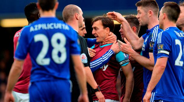 Chelsea's Spanish midfielder Cesc Fabregas (centre L) clashes with West Ham United's English midfielder Mark Noble (centre R) during the English Premier League football match between Chelsea and West Ham United at Stamford Bridge