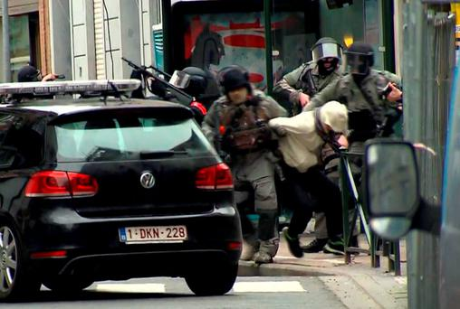 Abdeslam brought into custody by armed officers after they raided an apartment in the Molenbeek neighbourhood of Brussels on Friday