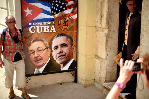 A tourist poses for a picture with a sign placed at the entrance of a restaurant with the images of Cuban and US Presidents Raul Castro and Barack Obama in Havana, Cuba. AFP PHOTO/ Yuri CORTEZ