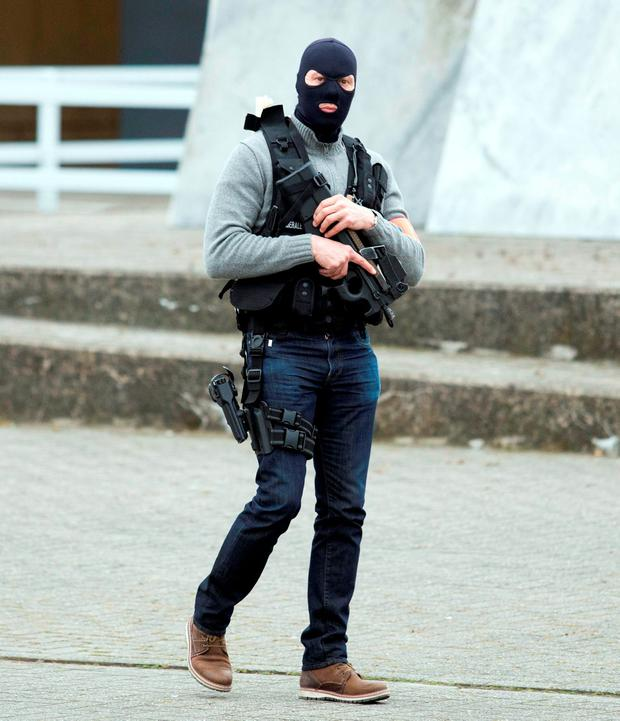 A special forces police officer awaits a convoy and ambulance thought to be carrying captured fugitive Salah Abdeslam outside the federal penitentary in Bruges, Belgium, on Saturday, March 19, 2016. Salah Abdeslam, the top suspect in last year's Paris attacks, was charged with terrorist murder on Saturday by Belgian authorities and his lawyer vowed to fight any attempt to extradite him to France to stand trial for the slaughter of 130 people