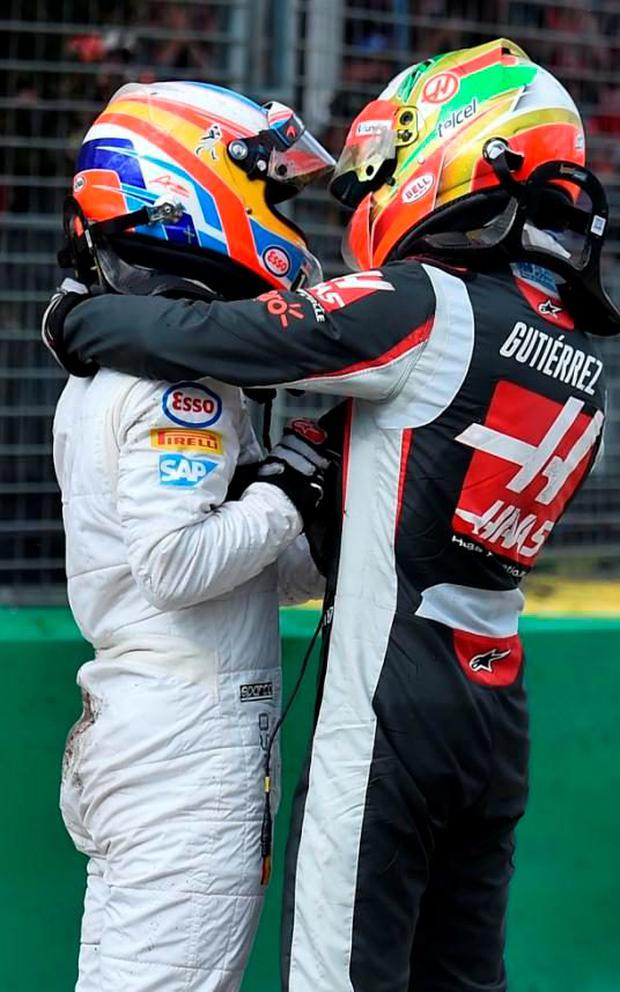The two unhurt drivers embrace after the crash