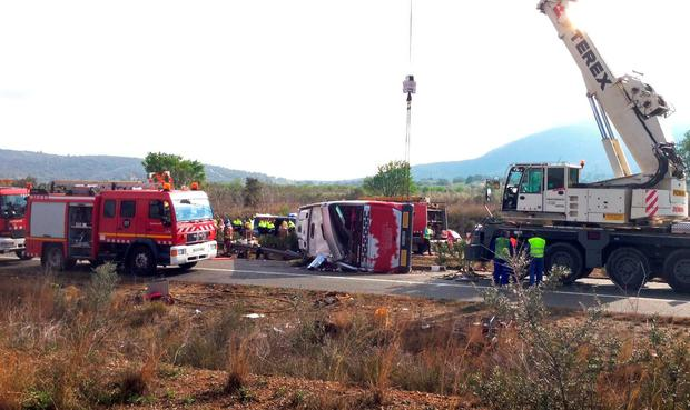 Emergency services personnel stand at the scene of a bus accident crashed on the AP7 highway that links Spain with France along the Mediterranean coast near Freginals halfway between Valencia and Barcelona early Sunday, Spain, March 20, 2016