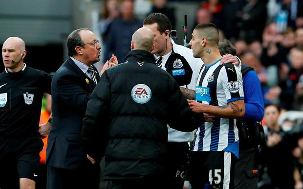 Newcastle United manager Rafael Benitez (left) stops Aleksandar Mitrovic (right) from returning to the pitch after suffering a head injury