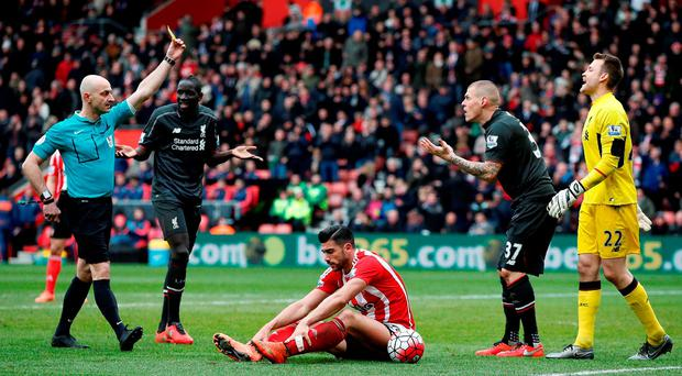 Referee Roger East (L) shows a yellow card to Liverpool's Slovakian defender Martin Skrtel (2R) following his challenge on Southampton's Italian striker Graziano Pelle (C)