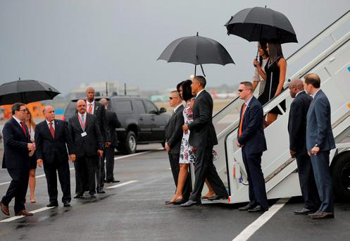 U.S. President Barack Obama and his wife Michelle approach Cuba's foreign minister Bruno Rodriguez (L) as they arrive at Havana's international airport for a three-day trip, in Havana REUTERS/Carlos Barria